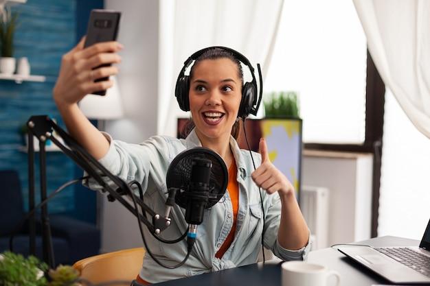Vrouw blogger, vlogger portret fotograferen van zichzelf op smartphone. content creator filmt voor mode- en beautyreview, plezier maken op social media-platform terwijl je selfie maakt