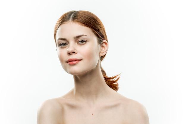 Vrouw blote schouders verzameld haar cosmetologie charme glimlach.