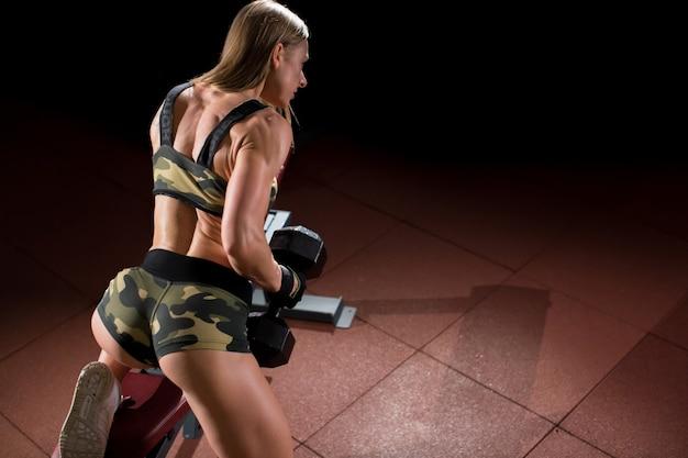 Vrouw bodybuilder in sportschool opheffing halters op bank