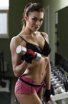 Vrouw bodybuilder training met halter.