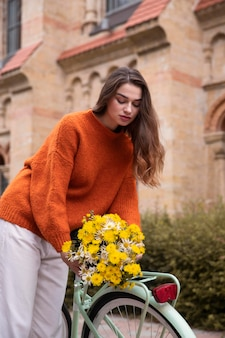 Vrouw boeket bloemen op de fiets te zetten
