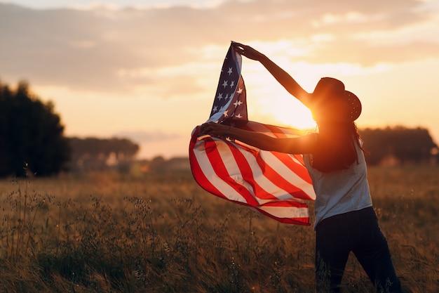 Vrouw boer in de landbouw met amerikaanse vlag op zonsondergang
