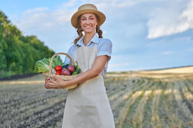 Vrouw boer strooien hoed schort staande landbouwgrond glimlachen