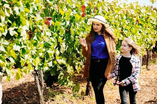 Vrouw boer wijnmaker met kind dochter om te lopen tussen de rijen met wijnstokken jonge moeder met hoed o...