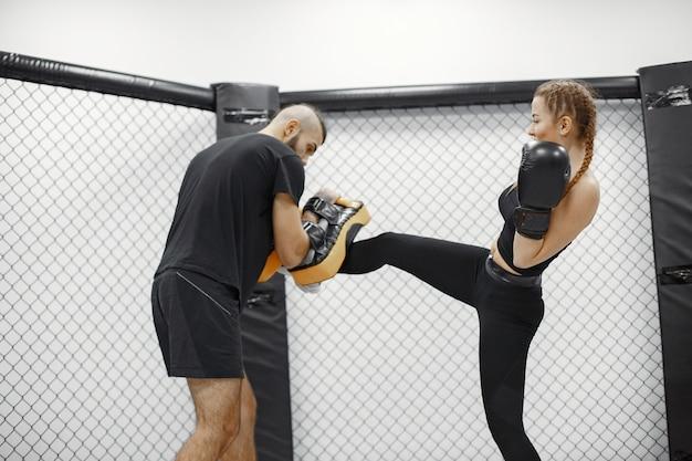 Vrouw boksen. beginner in een sportschool. dame in zwarte sportkleding. vrouw met coach.
