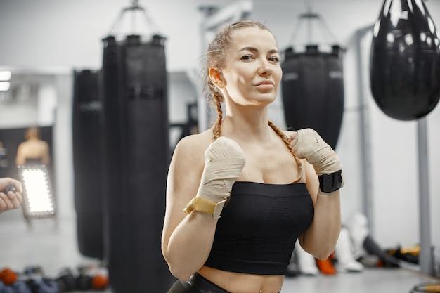 Vrouw boksen. beginner in een sportschool. dame in zwarte sportkleding.