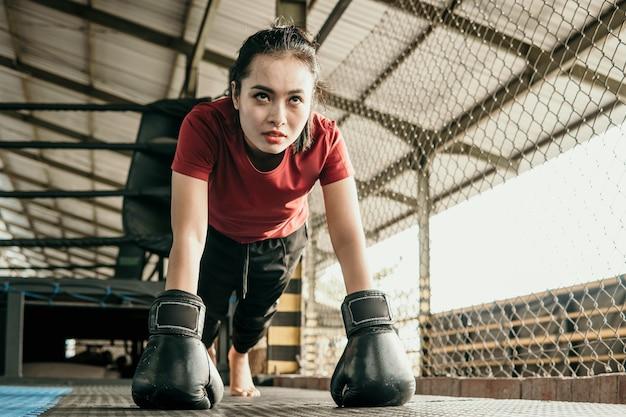 Vrouw bokser die zwarte handschoen draagt, pusht zich tijdens het opwarmen voordat hij deelneemt aan de achthoek