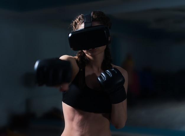 Vrouw bokser fit meisje in vr-bril bokshandschoenen in opleiding boksspel in virtual reality