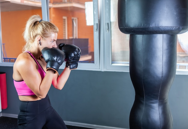 Vrouw bokser in bokshandschoenen slaat een bokszak
