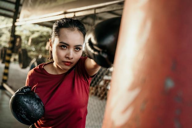 Vrouw bokser vechter doen oefening slaan bokszak met copyspace op bokskamp