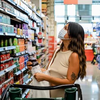 Vrouw boodschappen doen, supermarkt stockafbeelding