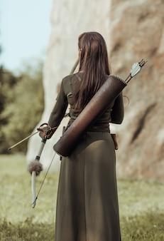 Vrouw boogschutter met pijlen op haar rug, staat met haar rug naar de kijker