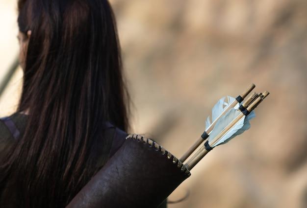 Vrouw boogschutter permanent met haar rug met pijlkoker voor pijlen
