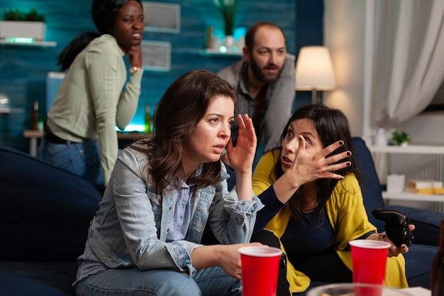 Vrouw boos na verlies bij online videogames terwijl ze 's avonds laat socialiseert met een multi-etnische groep vrienden in de woonkamer thuis, bier drinkend.