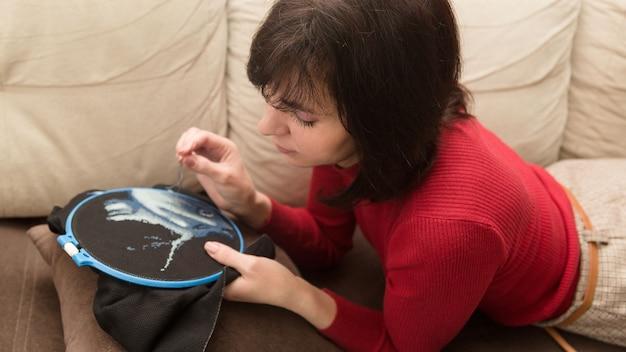 Vrouw borduurt een afbeelding in kruissteek op stof.