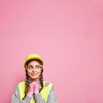 Vrouw bouwer assistent houdt handen bij elkaar kijkt naar boven peinzend denkt over de bouw van een nieuw gebouw draagt beschermende helm veiligheidsbril en uniform geïsoleerd over roze muur.