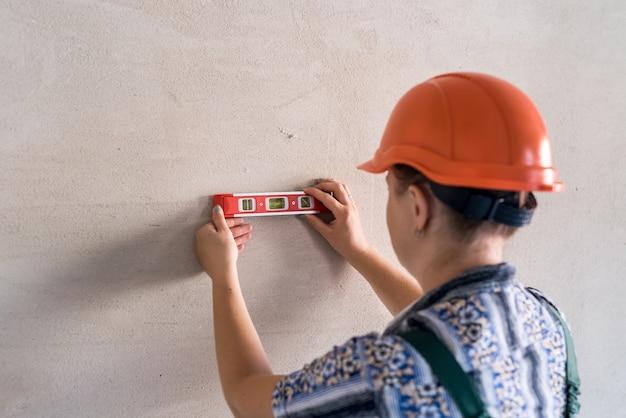 Vrouw bouwer meet muur met waterpeil gereedschap