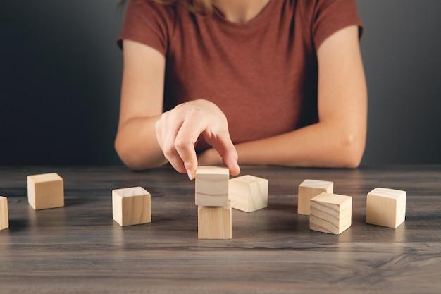 Vrouw bouwt van houten kubussen