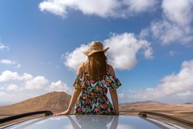Vrouw bovenop een auto die naar het prachtige landschap van fuerteventura, canarische eilanden, spanje, selectieve focus kijkt