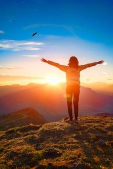 Vrouw bovenop een berg bij zonsondergang kijkt adelaar