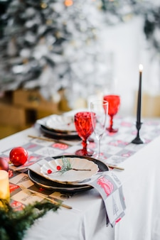 Vrouw brand kaarsen. kersttafel instelling in traditionele kleuren