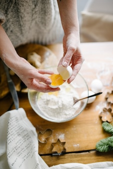 Vrouw breekt een ei en voegt toe aan de bloem. proces koken.
