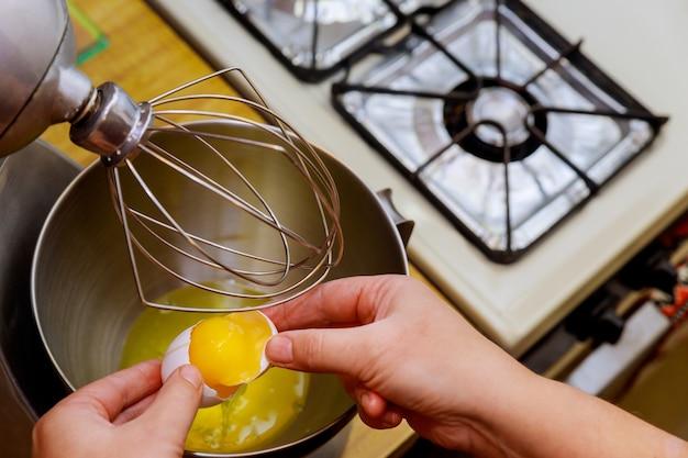 Vrouw breekt het ei in een mengkom en scheidt het eiwit van de eierdooiers