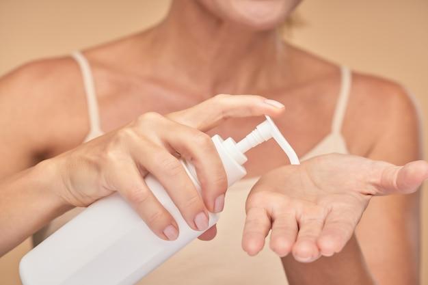 Vrouw brengt crème aan op haar handpalm