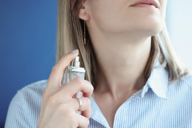 Vrouw brengt eau de toilette aan in haar nek