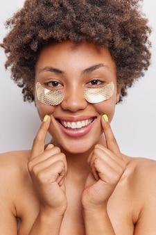 Vrouw brengt gouden vlekken onder de ogen aan om rimpels te verminderen glimlacht breed toont witte tanden staat shirtless geniet van schoonheidsprocedures poseert binnenshuis