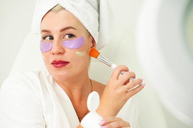 Vrouw brengt make-up aan op haar gezicht, selectieve focus op huid en penseel brengt foundation aan op gepigmenteerde ... Premium Foto