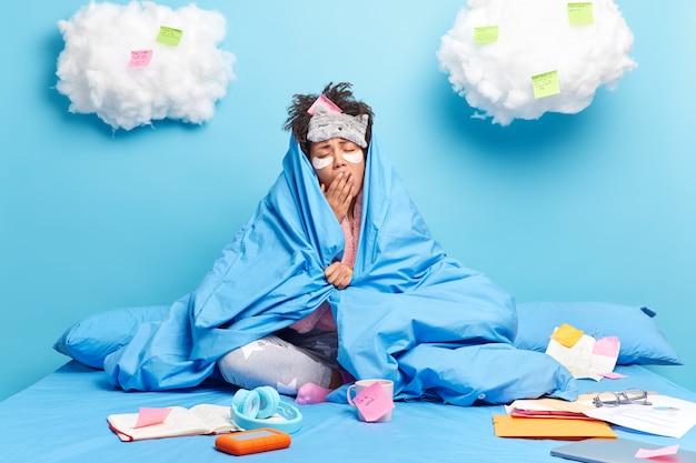 Vrouw brengt schoonheidspleisters aan gaapt terwijl ze werkt tot in de late uurtjes gewikkeld in deken bereidt zich voor op eindexamens