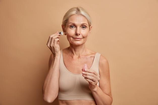 Vrouw brengt serum op gezicht aan is kalm serieuze uitdrukking heeft huidbehandeling gebruikt effectief cosmetisch product draagt bijgesneden top geïsoleerd op bruin