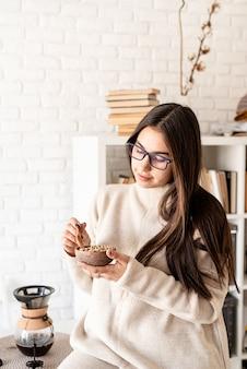 Vrouw brouwen van koffie in koffiepot, groene koffiebonen ruiken