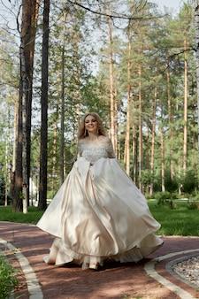 Vrouw bruid in een luxe gezwollen trouwjurk loopt langs het pad naar de bruiloft