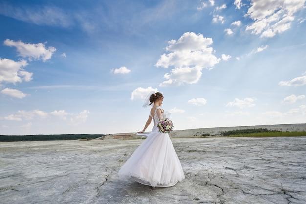 Vrouw bruid in trouwjurk in woestijn dansen