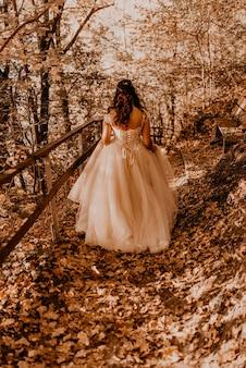 Vrouw bruid in witte trouwjurk met kapsel make-up en kroon op haar hoofd loopt door herfst bos op gevallen oranje bladeren