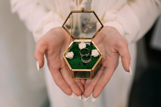 Vrouw bruid met trouwringen in een doos op haar handen