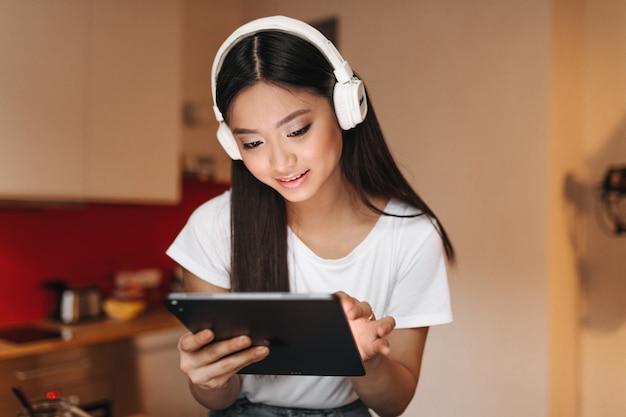 Vrouw brunette in witte top en koptelefoon in goed humeur kijkt naar het scherm van de tablet