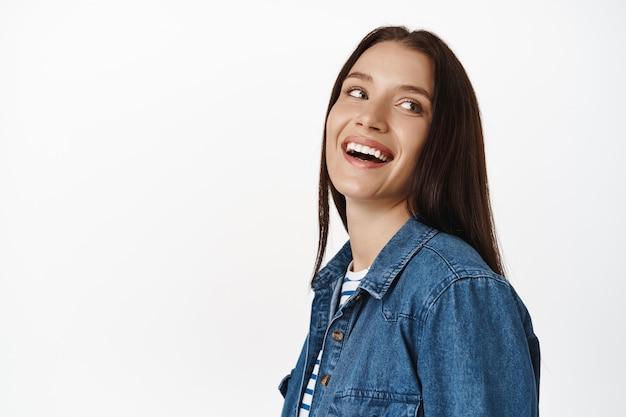 Vrouw, brunette model lachend en glimlachend witte tanden, schone gloeiende huid van volwassen vrouw, zorgeloos opzij kijkend, staande over wit