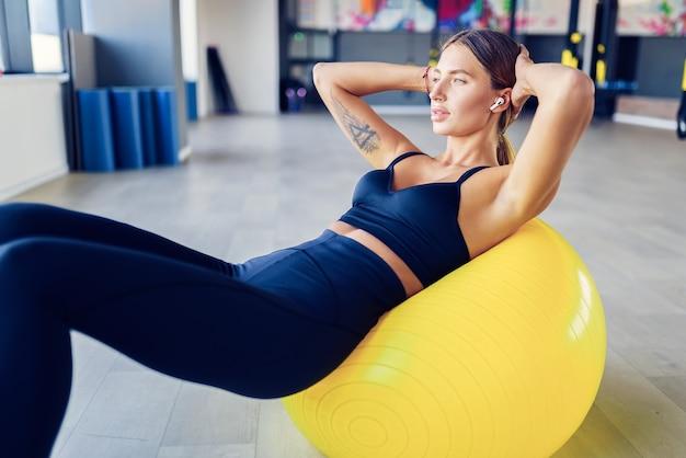 Vrouw buik crunches pilates oefening op oefening fitness bal op sportschool doet. oefeningen voor de buikspieren. zwitserse bal. inspanning, toewijding en motivatie concept.