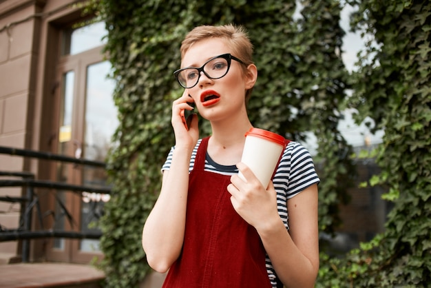 Vrouw buiten een kopje koffie zomervakantie communicatie aan de telefoon