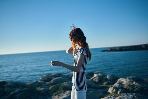 Vrouw buiten in de bergen kijkend naar het zee strand zomervakantie landschap