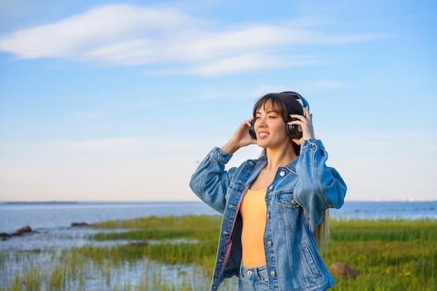 Vrouw buiten in de natuur luisteren naar muziek op de koptelefoon
