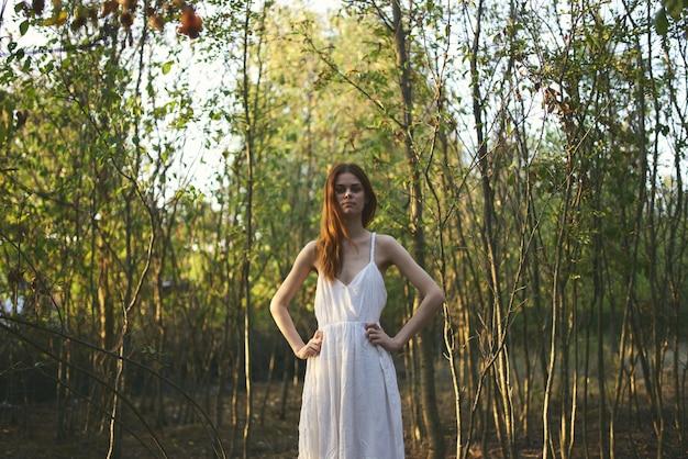 Vrouw buiten in het bos bomen zomer witte jurk