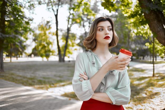 Vrouw buiten met een kopje koffie op straat