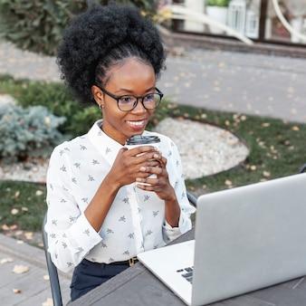 Vrouw buiten werken op laptop