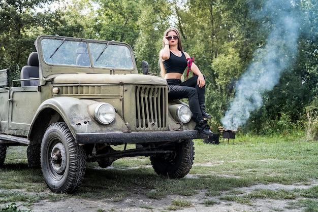 Vrouw buiten zittend op de motorkap van militaire auto