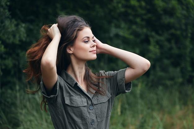 Vrouw buitenshuis frisse lucht houdt handen in de buurt van het reisgezicht groene bladeren bijgesneden weergave