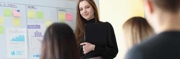 Vrouw business coach staande op het bord voor studenten luisteraars